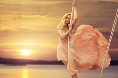 Pretty lady on a swing above the ocean Stock Images