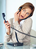 Pretty lady talking on both telephone Stock Images