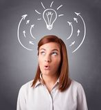 Pretty lady thinking with arrows and light bulb overhead Royalty Free Stock Photo
