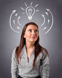 Pretty lady thinking with arrows and light bulb overhead Stock Images