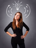 Pretty lady thinking with arrows and light bulb overhead Royalty Free Stock Images