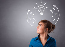 Pretty lady thinking with arrows and light bulb overhead Royalty Free Stock Photos