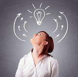 Pretty lady thinking with arrows and light bulb overhead Royalty Free Stock Photography