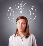 Pretty lady thinking with arrows and light bulb overhead Stock Photo