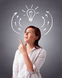 Pretty lady thinking with arrows and light bulb overhead Stock Image