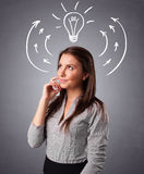Pretty lady thinking with arrows and light bulb overhead Stock Photography