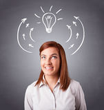 Pretty lady thinking with arrows and light bulb overhead Royalty Free Stock Image