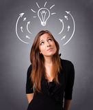 Pretty lady thinking with arrows and light bulb overhead Stock Photos