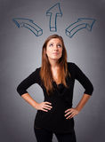Pretty lady thinking with arrows overhead Royalty Free Stock Photos