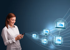 Pretty lady typing on smartphone with cloud computing Royalty Free Stock Image