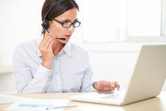 Pretty latin employee talking on headphones Royalty Free Stock Photo