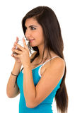 Pretty latin girl drinking water from a glass. Pretty latin long haired smiling girl drinking water from a glass isolated on white stock images