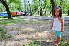 Pretty latin kid with a train at the background. Pretty latin little girl with a train at the background Stock Image