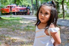 Pretty latin kid with a train at the background. Pretty latin little girl with a train at the background Royalty Free Stock Image