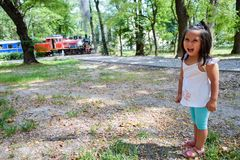 Pretty latin kid with a train at the background. Pretty latin little girl with a train at the background Stock Images