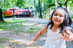 Pretty latin kid with a train like background. Pretty latin little girl with a train like background Royalty Free Stock Image