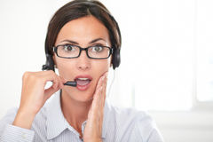 Pretty latin secretary conversing on headphones Royalty Free Stock Image