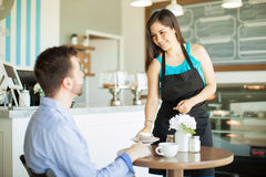 Pretty Latin waitress serving a cupcake Royalty Free Stock Images