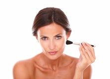 Pretty latin woman applying make up Stock Image
