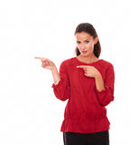 Pretty latin woman pointing to her right Royalty Free Stock Photo