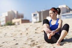 Pretty runner woman runner sitting on sandy beach stock images