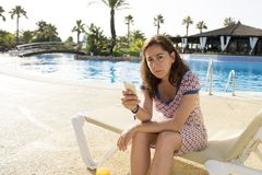 Pretty latin woman sad on her smart phone on holidays. Pretty attractive latin woman unhappy and stressed on her smart phone by the pool on holidays at a resort Royalty Free Stock Image