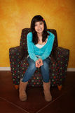Pretty Latina Girl. Seated on Colorful Chair Stock Photo