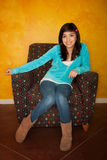 Pretty Latina Girl. Seated on Colorful Chair Royalty Free Stock Image