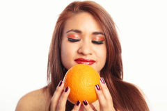 Pretty Latina Woman Smelling an Orange Stock Photography