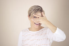 Pretty laughing girl covered face with her hands and peeking through her fingers.  Royalty Free Stock Photography