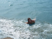 Pretty laughing girl in foaming waves of blue sea Stock Images