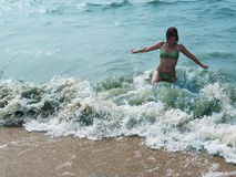 Pretty laughing girl in foaming waves of blue sea Stock Photos