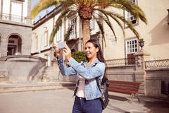 Pretty laughing girl taking pictures on cell phone Royalty Free Stock Photography