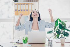 Pretty, laughing lawyer with raised arms and fists celebrating s. Uccessfully completed work, sitting om chair at her desk in work place Royalty Free Stock Photos