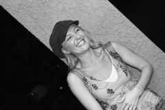 Pretty laughing woman. An attractive lady is outside at night laughing heartily and holding her belly Stock Photography