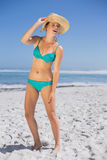 Pretty laughing woman in bikini on beach wearing sunhat Stock Photo