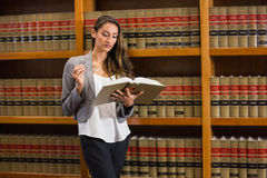 Pretty lawyer reading in the law library Stock Photos