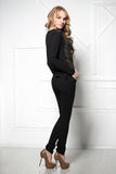Pretty leggy blond woman. In black clothes posing near white wall Royalty Free Stock Photo
