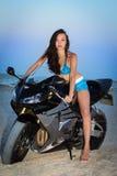 Pretty leggy brunette. Posing on the black motorbike Royalty Free Stock Photo