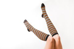 Pretty  legs in  a long multi-colored socks. Pretty legs in  a long multi-colored socks Stock Photography