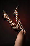 Pretty legs in a long multi-colored socks royalty free stock images