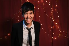 Pretty lesbian woman laughing, wearing suit and tie with lights background