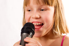 Pretty litle girl singing in microphone isolated o Royalty Free Stock Photos