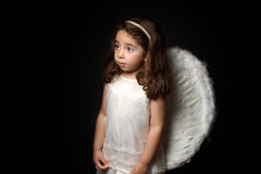 Pretty little angel looking sideways. Angelic little girl looking sideways with space for copy Stock Photo