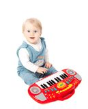 Pretty little baby girl. Pianist plays on a toy piano synthesizer isolated on white Royalty Free Stock Photography
