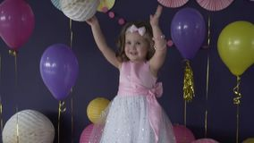 Pretty little baby girl laughing and playing with balloon on her birthday party stock video footage