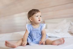 Pretty little baby girl sits on a bed and looks to side. Pretty little baby girl sits on bed and looks to side royalty free stock images