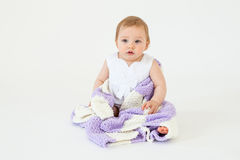 Pretty little baby girl sitting on floor with plaid isolated Stock Photos