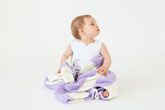 Pretty little baby girl sitting on floor with plaid isolated Royalty Free Stock Image