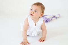 Pretty little baby girl sitting on floor with plaid Royalty Free Stock Photos